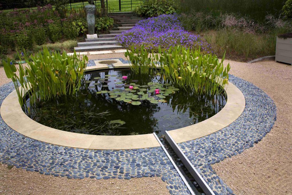 На фото пример оформления водоема в саду круглой формы, из камня и плитки, в стиле модерн.