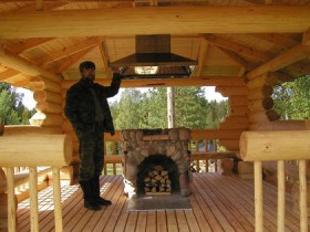 Wooden gazebo with barbecue in the center