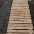 Economy version of the garden path: wooden walkway of pallets with their hands