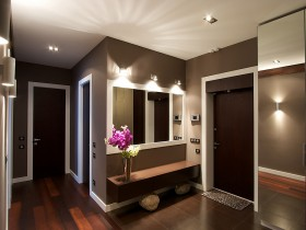 Small dark hallway with a bench and mirror