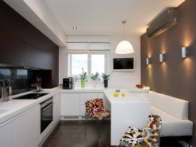 The interior white kitchen with the bright chairs
