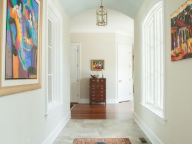 A long narrow hallway in light tones with colourful paintings