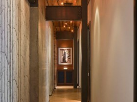 A long narrow hallway with white walls and wooden ceiling