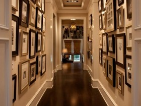 The walls of a narrow hallway, decorated with photos