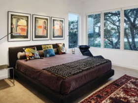 Bright bedroom with dark bed and colourful paintings