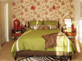 Bedroom with green bedding and Wallpaper with floral ornament