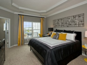 Grey bedroom with black bed and yellow accessories