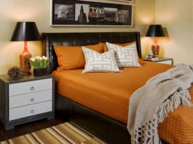 Bedroom with black bed and orange pastel linen