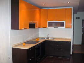 Orange and black furniture in white kitchen