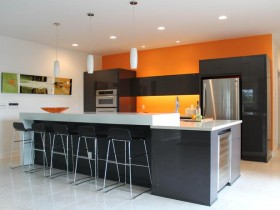 Modern bright kitchen with black furniture and orange wall