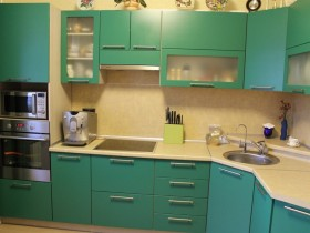 The interior of the small bright kitchen with green furniture