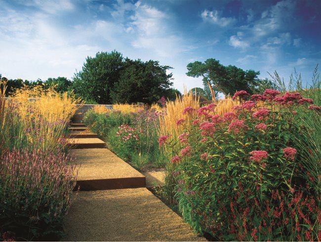 Брэдли-Хоул на традиционный сад, обнесенный стеной, где сетка из стали краем дорожки содержит сложные заносы трав и многолетников.