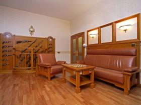 Классическая гостиная с кожаным диваном и оружейным стендом