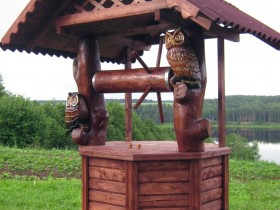 Wooden well carved owls