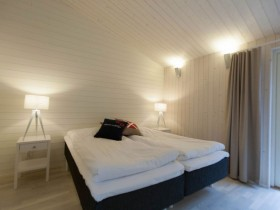 White bedroom with black bed in Scandinavian style