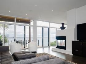 Світла сучасна вітальня з каміном і великими вікнами