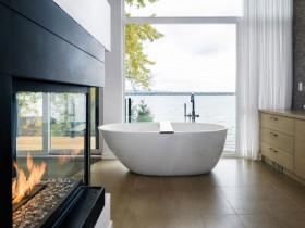 Біла ванна овальної форми поруч з каміном