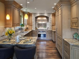 Wood kitchen cabinetry with marble countertops