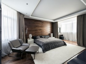 Spacious modern bedroom with suspended ceiling and wooden wall