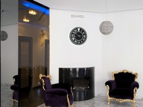 Black armchairs with gilding on a background of white walls in the apartment