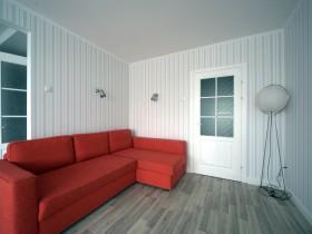 Світла вітальня з великим червоним диваном