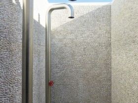 Modern outdoor shower, lined with pebbles
