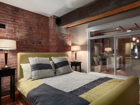 Stylish bedroom with exposed brick walls and bright bed