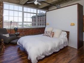 Светлая спальня с кирпичными стенами