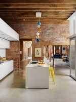 Кухня с кирпичными стенами и белой мебелью