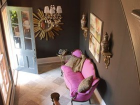 The interior of a small dark hallway with pink sofa