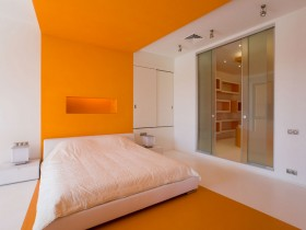 Orange bedroom with white bed