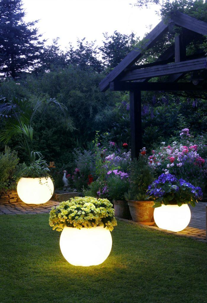 Нижняя креативная подсветка садового участка со ступенькой и переходом на уровень ниже, лампами - шарами - вазонами.