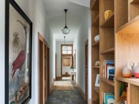 Long bright hallway with painting and wood bookshelf