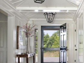 Large white hallway with black chandeliers