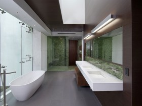 Bathroom with wooden walls and white bathtub