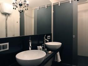 Белые умывальники в темной ванной комнате