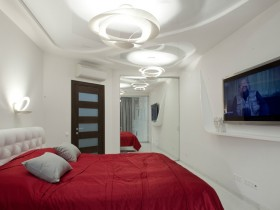 White bedroom with red bed