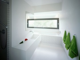 White bathroom, which is decorated with green towels