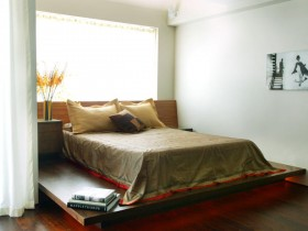 Wooden bed against white walls and floors