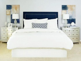 White bedroom with colourful paintings
