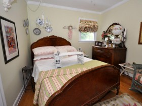 Маленькая светлая спальня с темной деревянной мебелью