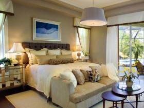 Светлая спальня с мягкой кроватью и диванчиком