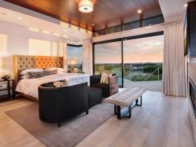Большая светлая спальня с многоуровневым деревянным потолком и большими окнами