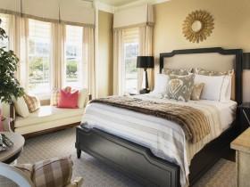 Интерьер спальни в теплых оттенках с большими окнами и диваном