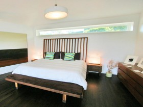 The contrast of dark wood with white walls in the interior bedroom