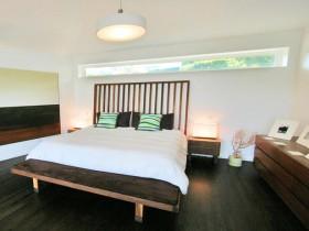 Контраст темного дерева с белыми стенами в интерьере спальни
