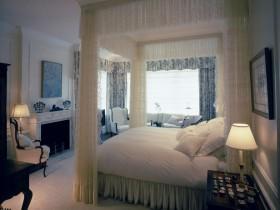 Интерьер светлой спальни с камином и кроватью под балдахином