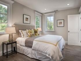 Светло-серая спальня с белой кроватью