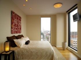 Маленькая светлая спальня с большими окнами
