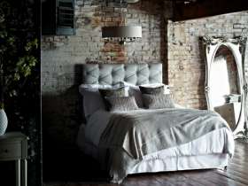Dark bedroom with mirror and brick wall